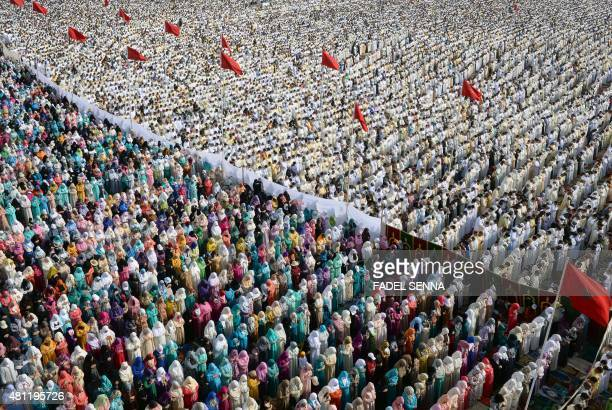 Moroccan Muslim women and men perform prayers for Eid alFitr which marks the end of the Muslim holy fasting month of Ramadan in the city of Sale...