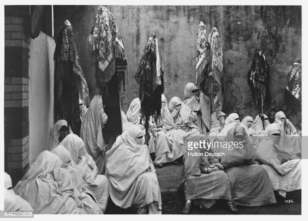 Moroccan Muslim women wearing burkas hold banners