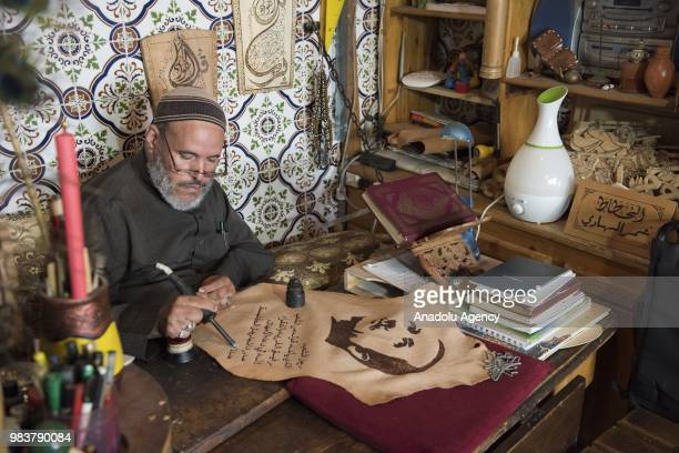 Moroccan Omer alHadi draws a calligraphy of Turkish President Recep Tayyip Erdogan on a leather after his presidential election success in Kenitra...