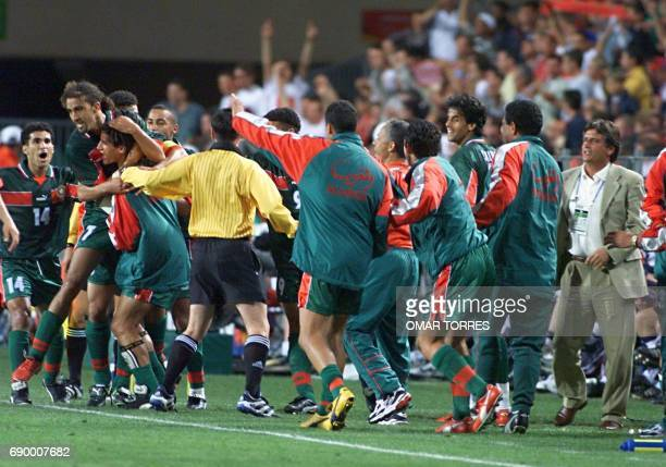 Moroccan players and national coach team Henri Michel jubilate after the goal of Moustafa El Hadji 10 June at the Stade de la Mosson in Montpellier...