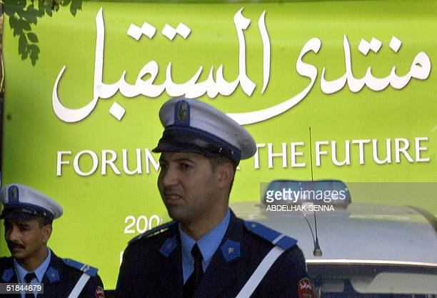 Moroccan police officers stand by the poster of 'Forum for the Future' in Rabat 10 December 2004 a day before Morocco was set to open its doors to...