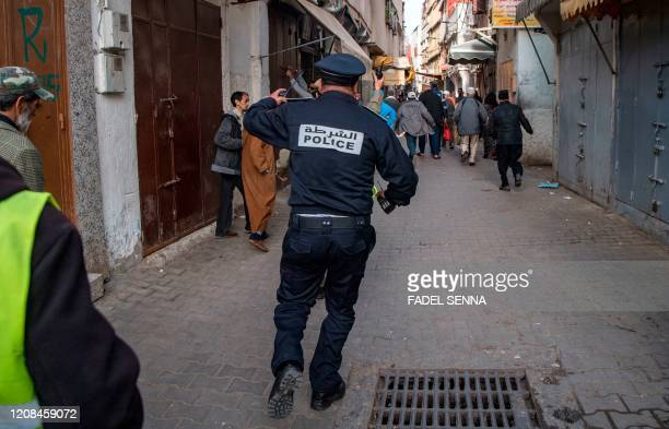 Moroccan policeman, patrolling as part of a larger combined security force, chases after people to instruct them to return to and remain at home as a...