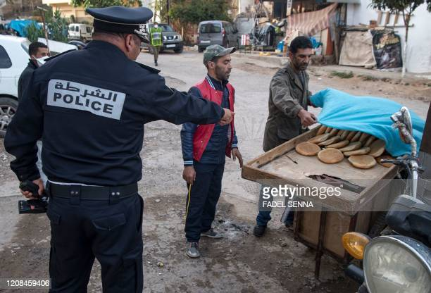Moroccan policeman, patrolling as part of a larger combined security force, orders a bread vendor to cover his cart, pack his goods, and return home...