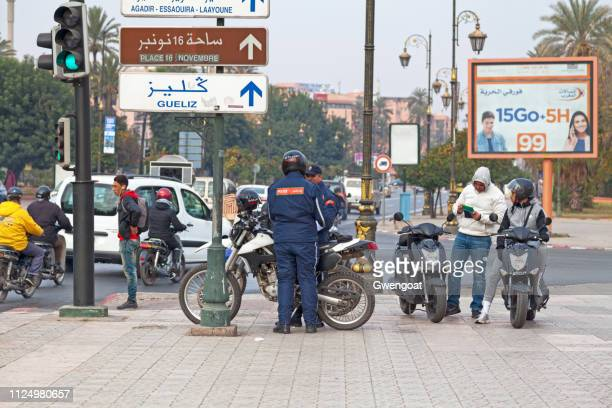 Moroccan policemen controlling the identity papers of two scooter riders