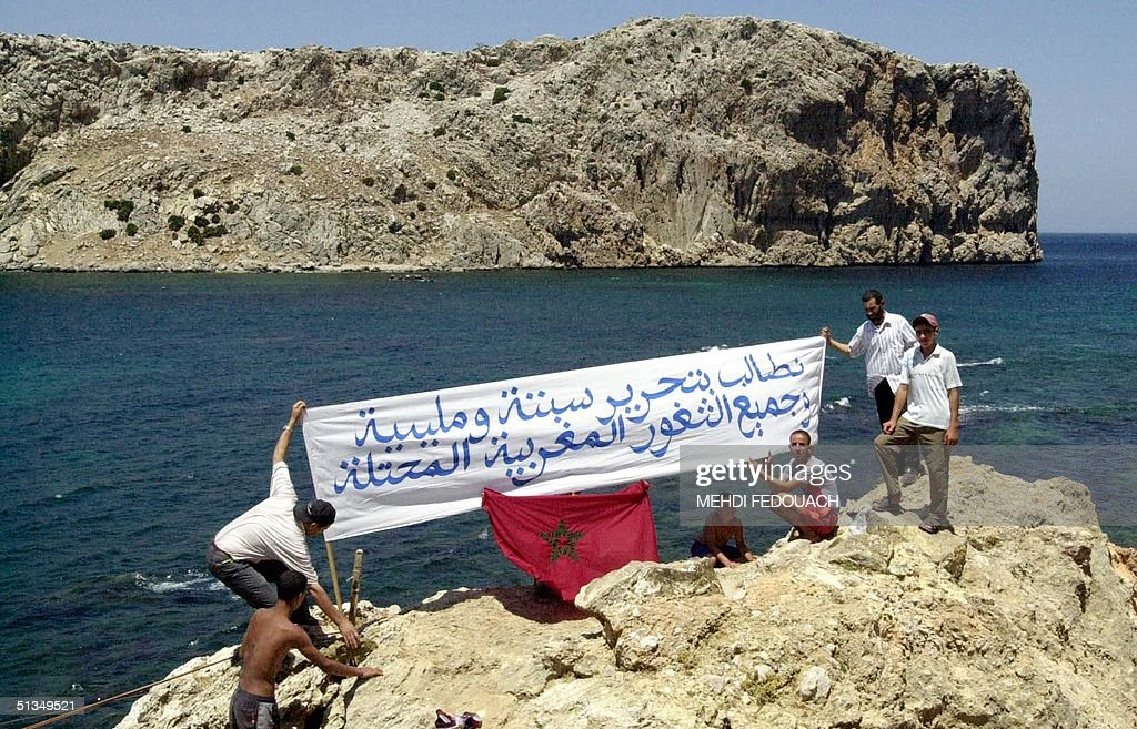 Moroccan protesters wave a banner reading: 'We demand the liberation of Ceuta and Melilla and of all Morrocan occupied territories' 21 July 2002 on the Moroccan coast in front the Perejil island. Around 400 Moroccans rallied 21 July on a promontory in Jbel Moussa to protest what they called the Spanish military invasion of the Perejil island. Morocco and Spain were to meet in Rabat 22 July to firm up a US-brokered accord reached at the weekend over Perejil that both claim as their territory.