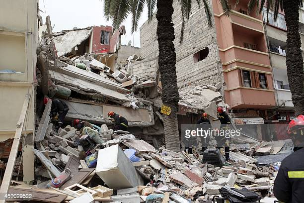Moroccan rescuers inspect the rubble of a residential building that collapsed on July 11 2014 in the Moroccan city of Casablanca Three buildings...