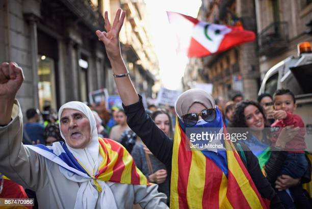 Moroccan Rif activists wrap themselves in a Catalan flag during a demonstration outside the Palau Catalan Regional Government Building on October 28...