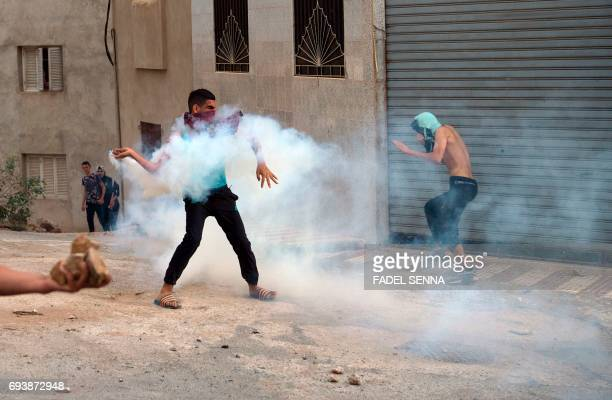 A Moroccan rif demonstrator prepares to throw a teargas canister back at security forces during clashes in the northern Moroccan city of AlHoceima on...