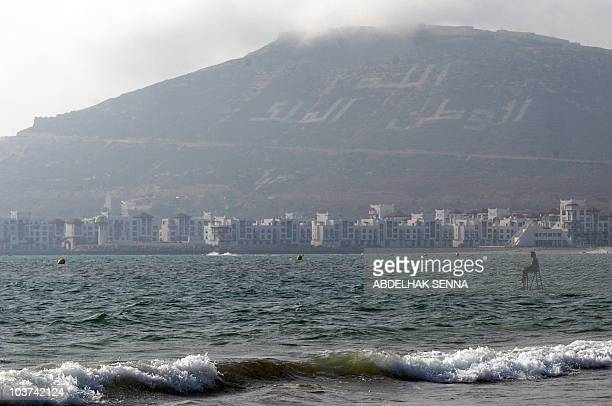 A Moroccan sits on a chair he placed in the sea on a beach in Agadir on August 22 2010 as he waits for Iftar which marks the breaking of a day long...