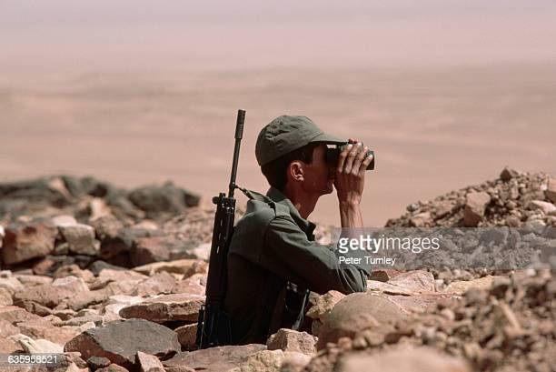 A Moroccan soldier looks through binoculars at the defense wall in GueltaZimmour on the lookout for members of the Polisario Morocco annexed and...