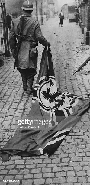 A Moroccan soldier trails a Nazi flag behind him in the streets of Mulhouse