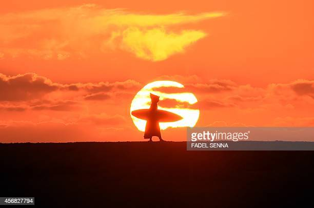 A Moroccan surfer walks along the beach as the sun sets in Oued Charrat 30 kilometres from the capital Rabat on October 7 2014 AFP PHOTO / FADEL SENNA