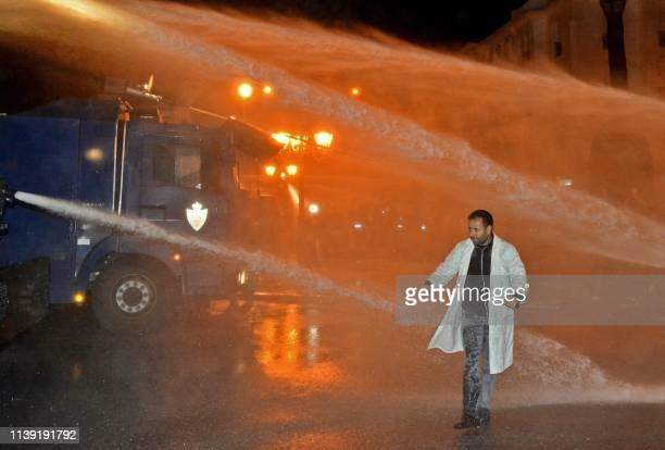 Moroccan teacher walks through a water spray from security forces' water cannon during a demonstration calling for permanent contracts within the...