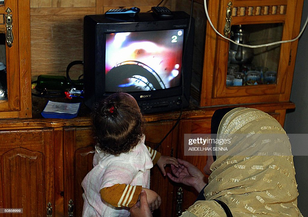 A Moroccan woman and her baby watch television in their makeshift home 18 May 2004 in a shantytown of Casablanca. The shack is lit with electricity provided in test areas by the utility LYDEC (Lyonnaise des Eaux de Casablanca). No electrical service is provided in shantytowns, and residents rely on communal street lighting, which they divert illegally to light their homes. In Casablanca alone, 400,000 people live in shantytowns.