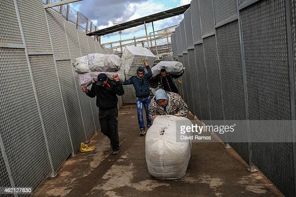 Moroccan woman carries a package on her back as she crosses the 'Barrio Chino' border crossing point between Melilla and Morocco on January 20 2015...