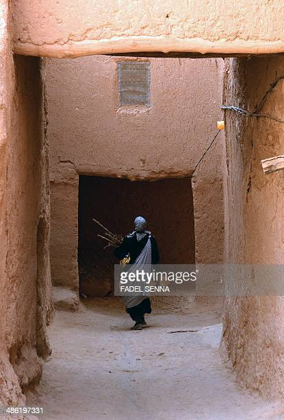 Moroccan woman carries wood as she walks along a narrow street in the Jewish Mellah quarter of Tinghir at the foot of the High Atlas and the heart of...