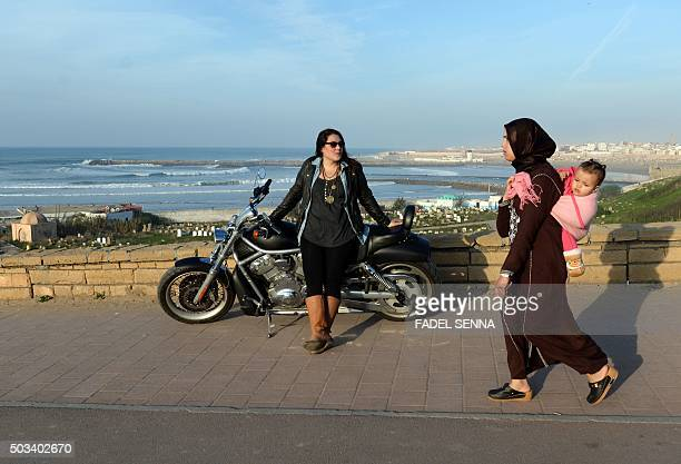 A Moroccan woman dressed in traditional attire walks past Mey Zniber a Moroccan therapist posing on her Harley Davidson motorbike on December 24 2015...