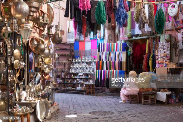 a moroccan woman dressed in typical dressing sitting outside a shop full of goods and souvenirs in the souk of marrakesh, morocco - street market stock pictures, royalty-free photos & images