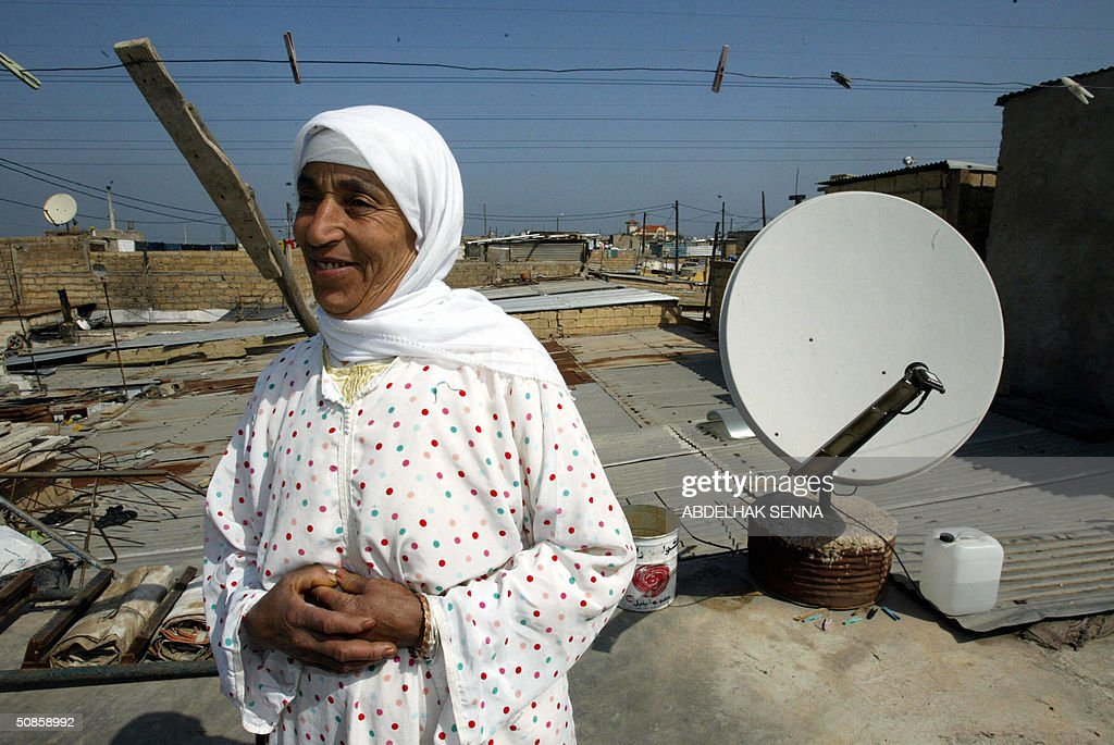 A Moroccan woman poses on the roof of her building with a satellite dish 18 May 2004 in a shantytown of Casablanca. The building is getting electricity provided in test areas by the utility LYDEC (Lyonnaise des Eaux de Casablanca). No electrical service is provided in shantytowns, and residents rely on communal street lighting, which they divert illegally to light their homes. In Casablanca alone, 400,000 people live in shantytowns.