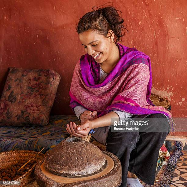 moroccan woman producing argan oil by traditional methods - marruecos fotografías e imágenes de stock