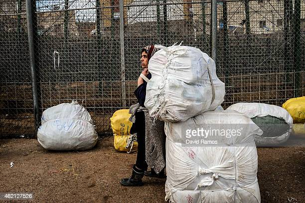 Moroccan woman rests with a package on her back as she crosses the 'Barrio Chino' border crossing point between Melilla and Morocco on January 20...