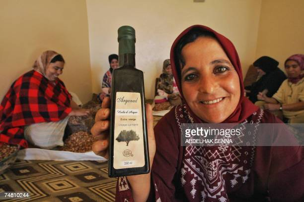 Moroccan woman shows a bottle of Argan oil as her colleagues crush Argan tree nuts 18 June 2007 in Smimmou near Essaouira to make Argan oil The Argan...
