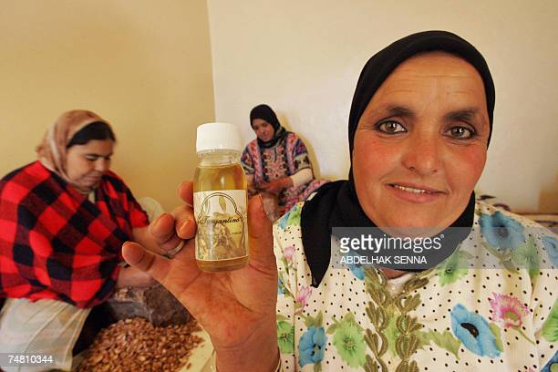 Moroccan woman shows a flacon of Argan oil for cosmetic use as her colleagues crush Argan tree nuts 18 June 2007 in Smimmou near Essaouira to make...