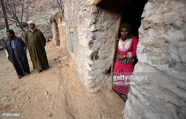 A Moroccan woman stands in the doorway of a house as men pass by in Taghzirt an isolated village in the elHaouz province in the High Atlas Mountains...