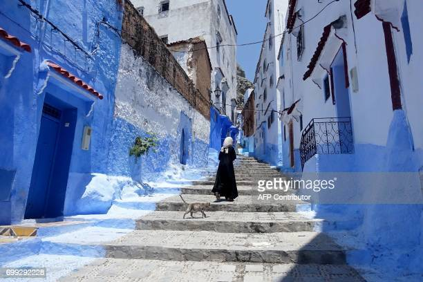 A Moroccan woman walks in Chefchaouen in the northern Moroccan Rif region during the Muslim holy fasting month of Ramadan on June 21 2017 Huddling...