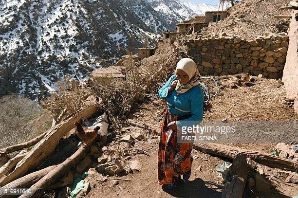 A Moroccan woman walks in Taghzirt an isolated village in the elHaouz province in the High Atlas Mountains south of Marrakesh on March 4 2016 When...