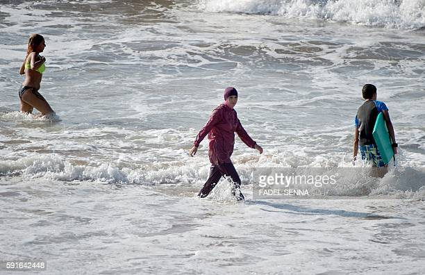 A Moroccan woman wearing a burkini a fullbody swimsuit designed for Muslim women enters the sea at Oued Charrat beach near the capital Rabat on...