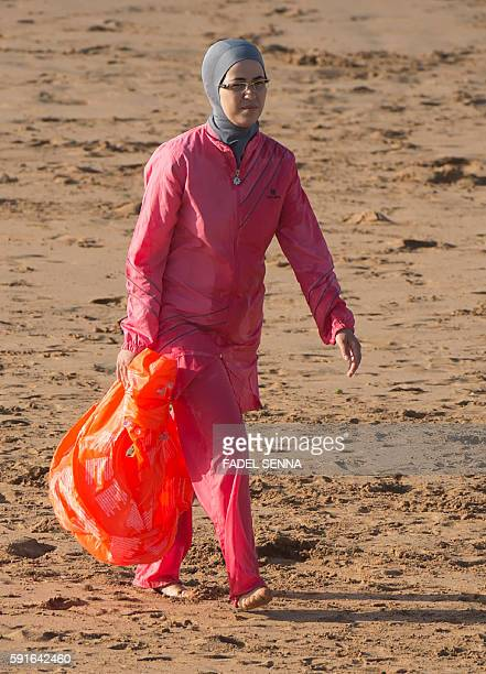 A Moroccan woman wearing a burkini a fullbody swimsuit designed for Muslim women walks at Oued Charrat beach near the capital Rabat on August 17 2016...