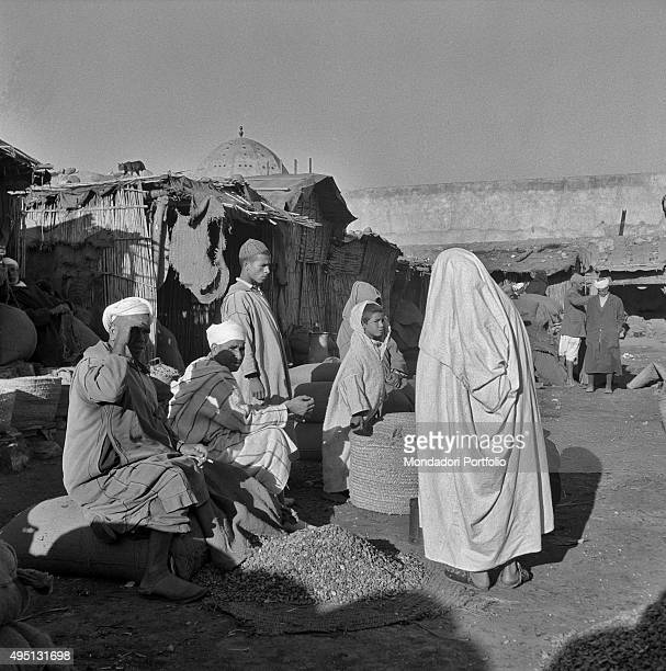 A Moroccan woman wearing the traditional clothes djellabah watches some merchants' goods in recent times in Morocco some women have started to assert...