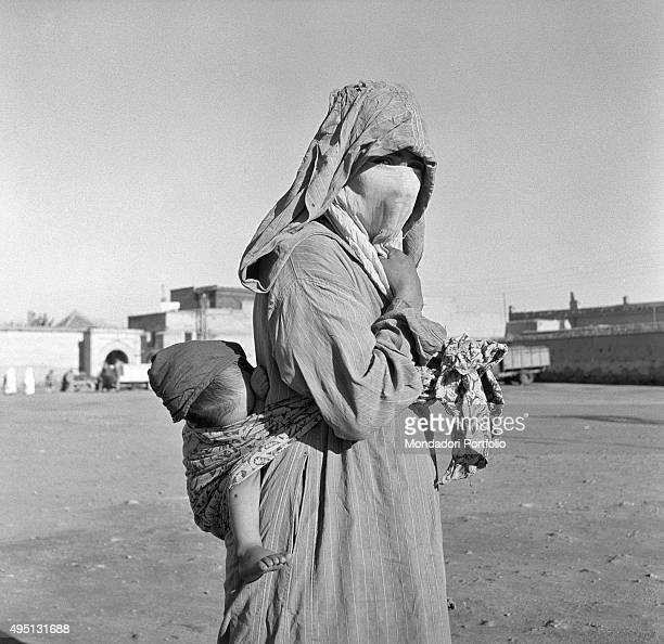 A Moroccan woman wearing the veil and the traditional clothes called djellabah looks at the camera carrying her child on her back in recent times in...