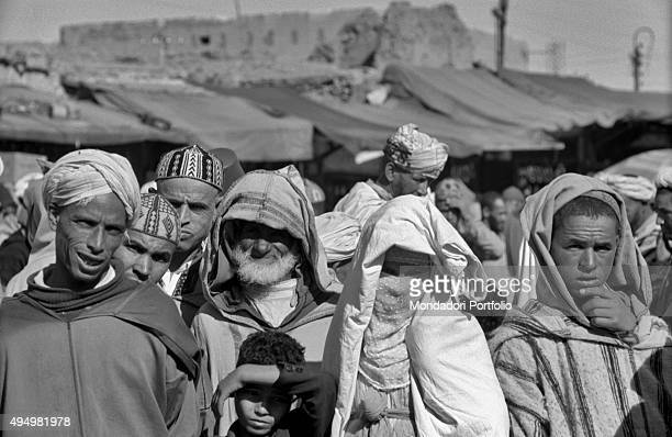 A Moroccan woman who wear the traditional clothes called djellabah and the veil that covers her face peacefully poses among other men in public this...