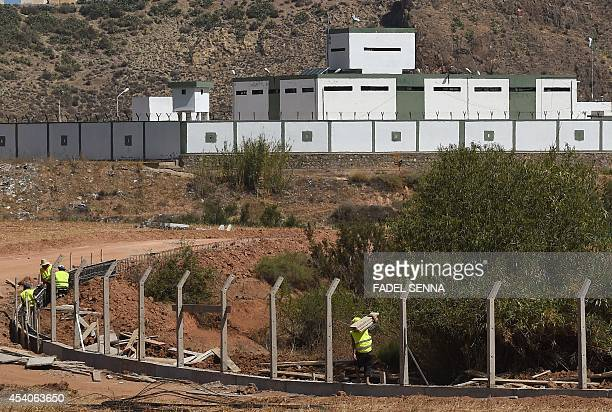 OUALI Moroccan workers build a border fence near an Algerian military post along the MoroccanAlgerian border on August 23 2014 near the Moroccan city...