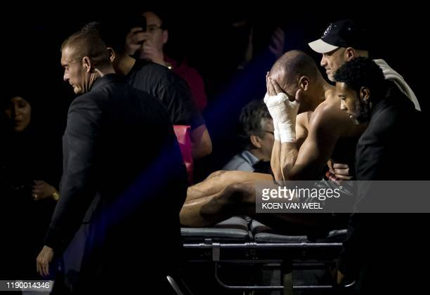 Moroccan-born Dutch kickboxer Badr Hari reacts after giving up following an injury during his fight against Dutch kickboxer Rico Verhoeven as part of...