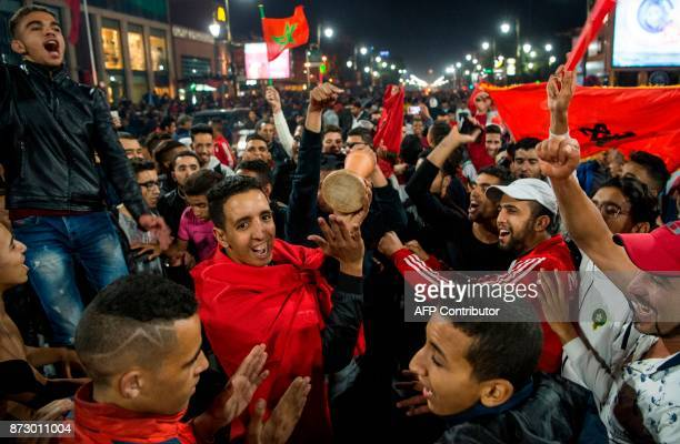 Moroccans celebrate November 11 2017 in Marrakech following Morocco's victory over Ivory Coast in their FIFA 2018 World Cup Africa Qualifier to...