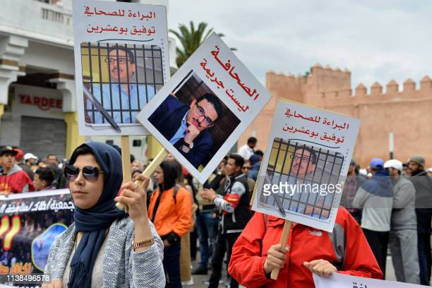 Moroccans hold posters bearing portraits of a convicted journalist during a demonstration against the court of appeal rulings on AlHirak alShaabi or...