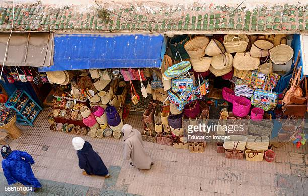 Moroccans in djellabas walking the Essaouira Medina with basket shop viewed from above