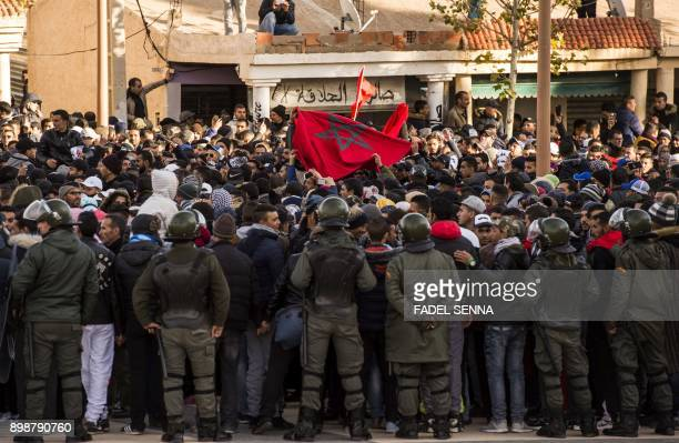 Moroccans shout slogans and wave a national flag as they participate in a demonstration after the funeral of two brothers who died while digging in...