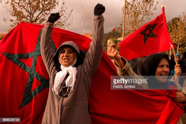 Moroccans shout slogans and wave their national flag as they participate in a demonstration after the funeral of two brothers who died while digging...