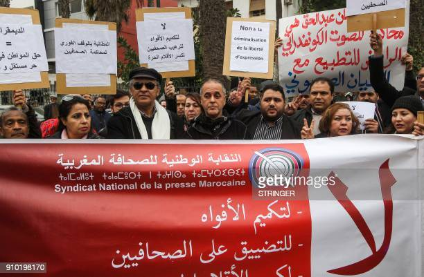 Moroccans shout slogans as they and stand behind a banner reading in Arabic No to gagging mouths no to retraints on journalists during a protest...