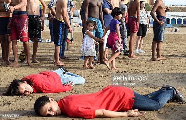 Moroccans walk past protesters adopting the position of the lifeless body of Syrian threeyearold Aylan Kurdi who drowned while fleeing the Syrian war...