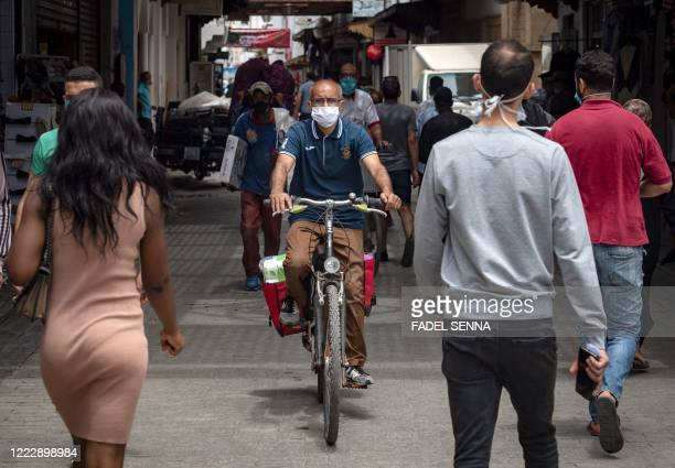 Moroccans wearing face masks walk along a street in the capital Rabat, after the authorities eased lockdown measures in some cities, that had been...
