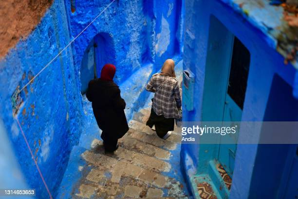 Morocco, Chefchaouen : Old women with veils going down the stairs in a lane of the Old Town. Houses with blue walls.