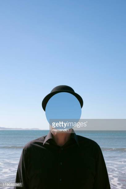 morocco, essaouira, man wearing a bowler hat with mirror in front of his face at the sea - surreal stock pictures, royalty-free photos & images