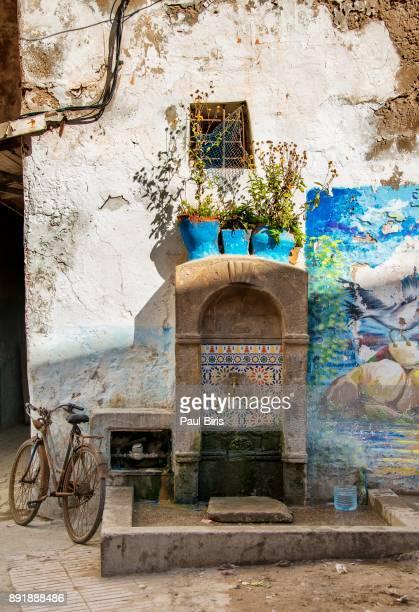 Morocco, Essaouira, Medina, Bicycle parked near a public fountain, UNESCO World Heritage Site