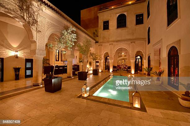 morocco, fes, hotel riad fes, courtyard with lightened pool by night - palace stock pictures, royalty-free photos & images