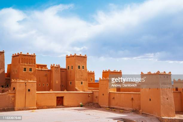 morocco, kasbah taourirt fortress on a sunny day with cloudy sky. - north africa stock pictures, royalty-free photos & images